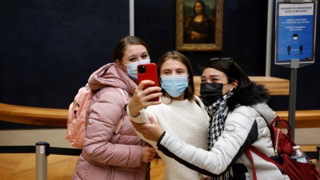 De máscara, visitantes fazem selfie com o quadro da Monalisa ao fundo, no Museu do Louvre, em Paris.